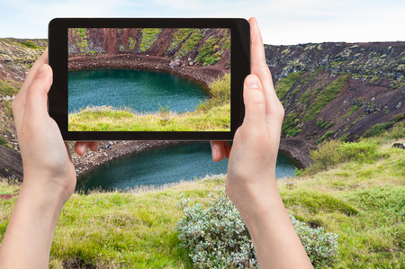 travel concept - tourist photographs old volcanic crater with Kerith lake in Iceland in september on tablet Stock Photo