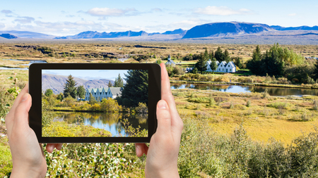 travel concept - tourist photographs rift valley in Thingvellir national park in Iceland in september on tablet