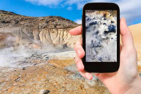 travel concept - tourist photographs mud acidic geyser in geothermal Krysuvik area on Southern Peninsula (Reykjanesskagi, Reykjanes Peninsula) in Iceland in september on smartphone