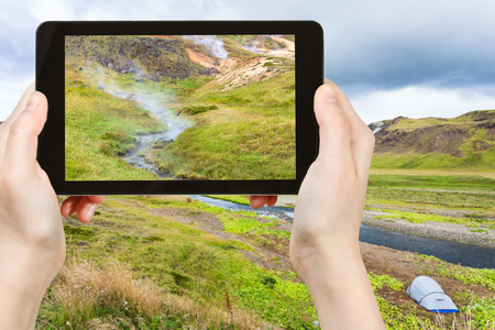 travel concept - tourist photographs valley of Varma river in Hveragerdi Hot Spring River Trail area in Iceland in september on tablet