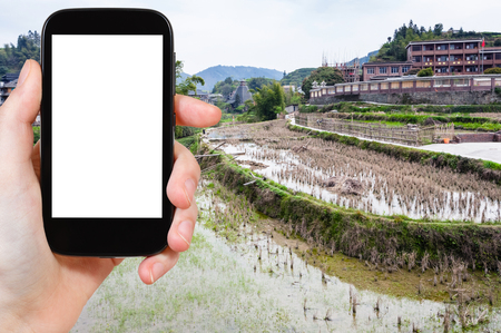 travel concept - tourist photographs terraced rice fields in Chengyang village of Sanjiang Dong Autonomous County in China in spring on tablet with cut out screen for advertising logo Stockfoto