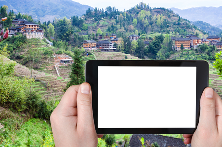 travel concept - tourist photographs Dazhai village with Rice Terraces in Longsheng (Dragons Backbone, Longji) county in China in spring season on smartphone with cut out screen for advertising Stock Photo