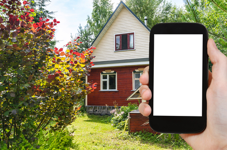 travel concept - tourist photographs simple wooden cottage and well on backyard in russian village in sunny summer day on smartphone 스톡 콘텐츠