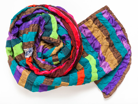 rolled stitched patchwork scarf from silk bands on white background Stock Photo
