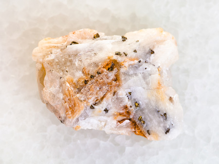 macro shooting of natural mineral rock specimen - native gold in raw quartz stone on white marble background