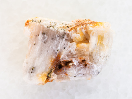 macro shooting of natural mineral rock specimen - native gold in rough quartz stone on white marble background