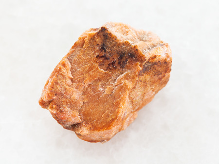 macro shooting of natural mineral rock specimen - rough orthoclase stone on white marble background