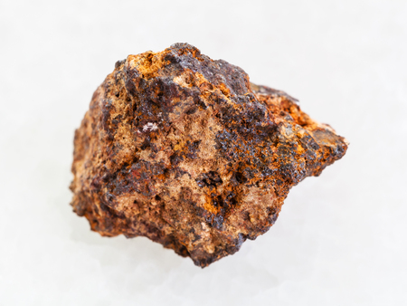 macro shooting of natural mineral rock specimen - raw Hematite (iron ore) stone on white marble background