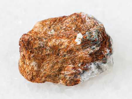 macro shooting of natural mineral rock specimen - piece of normandite stone on white marble background from Khibiny Mountains, Kola Peninsula, Russia Stock Photo