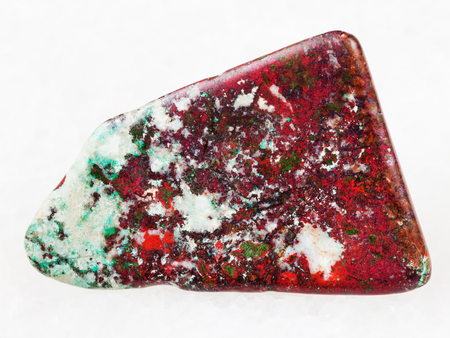 macro shooting of natural mineral rock specimen - tumbled red Cuprite and green Chrysocolla gemstone on white marble background from Milpillas mine, Mexico