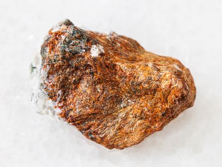 macro shooting of natural mineral rock specimen - raw normandite stone on white marble background from Khibiny Mountains, Kola Peninsula, Russia Stock Photo
