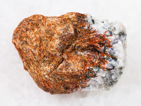 macro shooting of natural mineral rock specimen - rough normandite stone on white marble background from Khibiny Mountains, Kola Peninsula, Russia