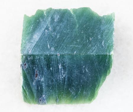 macro shooting of natural mineral rock specimen - raw nephrite stone slab on white marble background Reklamní fotografie