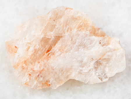 macro shooting of natural mineral rock specimen - raw belomorite stone (plagioclase moonstone) on white marble background from Karelia, Kola Peninsula in Russia Stock Photo