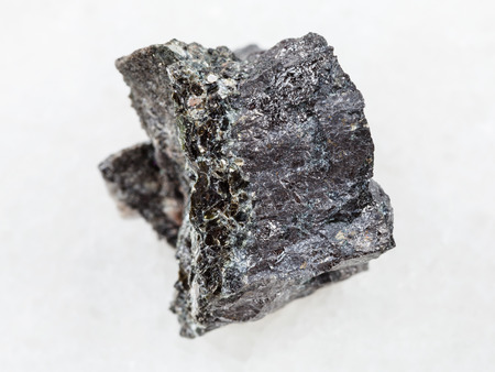 macro shooting of natural mineral rock specimen - raw Magnetite ore on white marble background from Kovdor, Karelia, Russia Banco de Imagens
