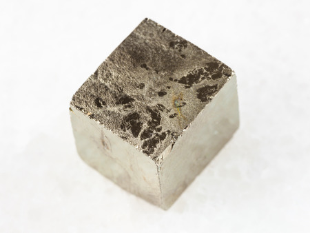 macro shooting of natural mineral rock specimen - pyrite crystal on white marble background from Spain