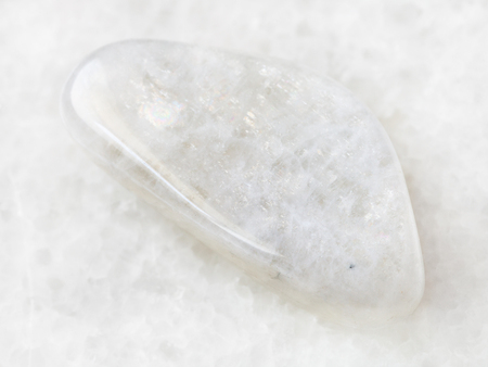 macro shooting of natural mineral rock specimen - tumbled white moonstone (adularia) gemstone on white marble background
