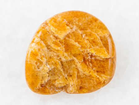 macro shooting of natural mineral rock specimen - polished Clinohumite gemstone on white marble background from Kuhilal district, Pamir Mountains , Tajikistan Stock Photo
