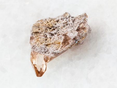 macro shooting of natural mineral rock specimen - crystal of topaz stone on white marble background from Brazil