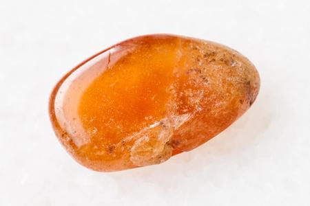 macro shooting of natural mineral rock specimen - polished Spessartine garnet gemstone on white marble background