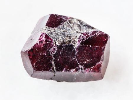 macro shooting of natural mineral rock specimen - rough crystal of red garnet gemstone on white marble background 版權商用圖片