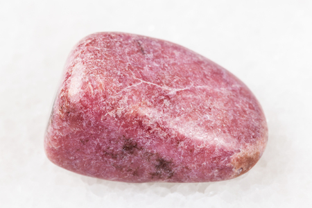 macro shooting of natural mineral rock specimen - polished rhodonite gem on white marble background from Ural Mountains