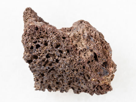 macro shooting of natural mineral rock specimen - rough Pumice of basic composition stone on white marble background