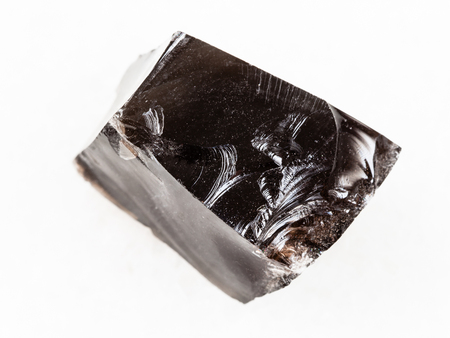 macro shooting of natural mineral rock specimen - piece of raw Obsidian (volcanic glass) stone on white marble background