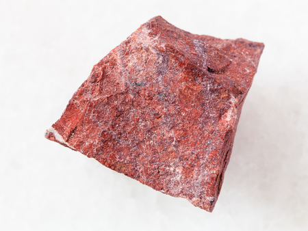 macro shooting of natural mineral rock specimen - rough red jasper stone on white marble background