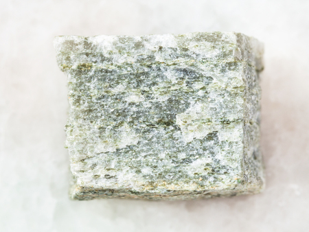 macro shooting of natural mineral rock specimen - quartz-mica schist stone on white marble background