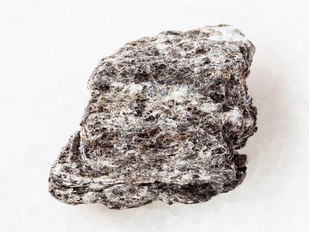 macro shooting of natural mineral rock specimen - piece of quartz-biotite schist stone on white marble background