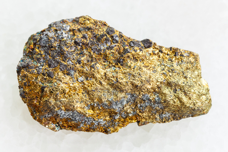 macro shooting of natural mineral rock specimen - rough pyrite ore on white marble background
