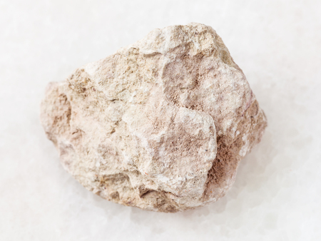 macro shooting of natural mineral rock specimen - raw marl stone on white marble background Stock Photo