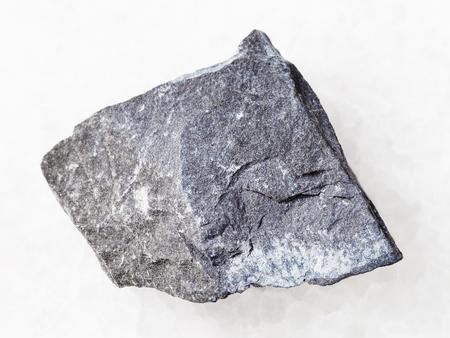 macro shooting of natural mineral rock specimen - rough argillite stone on white marble background
