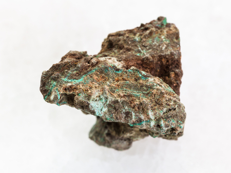 macro shooting of natural mineral rock specimen - rough Malachite (copper ore) stone on white marble background