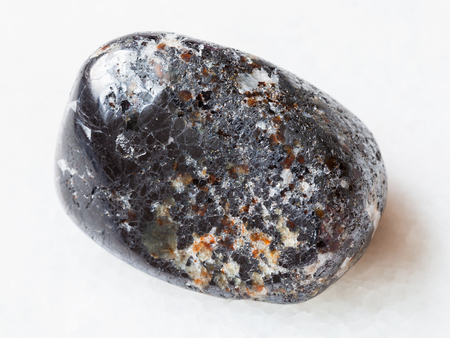 macro shooting of natural mineral rock specimen - tumbled magnetite stone on white marble background from Kovdor district of Kola Peninsula, Russia
