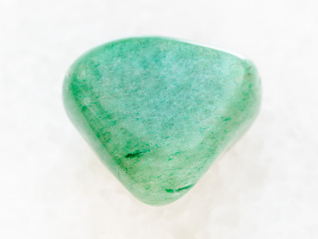 macro shooting of natural mineral rock specimen - tumbled green Aventurine gem on white marble background