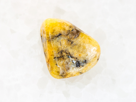 macro shooting of natural mineral rock specimen - tumbled yellow Agate gemstone on white marble background from Mexico