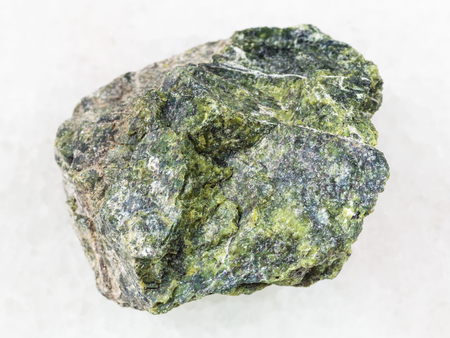 macro shooting of natural mineral rock specimen - raw serpentine stone on white marble background