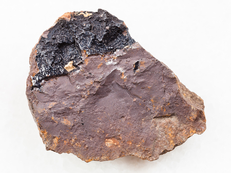 macro shooting of natural mineral rock specimen - concretion of goethite aggregates on limonite stone on white marble background from Olkhinskoye mine, Irkutsk region, Russia
