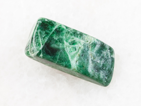 macro shooting of natural mineral rock specimen - tumbled green jadeite stone on white marble background from Itmurundy massif of Balkhash Region, Kazakhstan