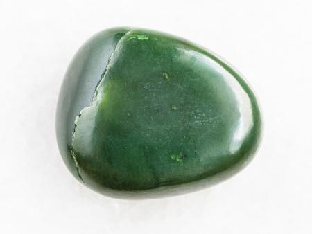 macro shooting of natural mineral rock specimen - tumbled green nephrite gemstone on white marble background Reklamní fotografie