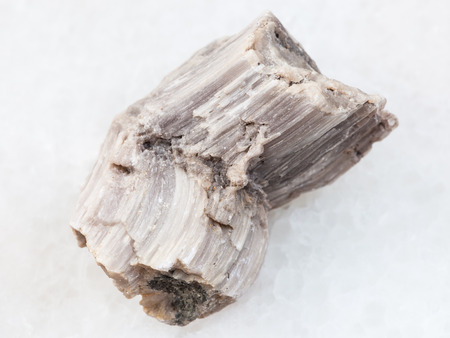macro shooting of natural mineral rock specimen - piece of baryte stone on white marble background from Irkutsk region, Russia