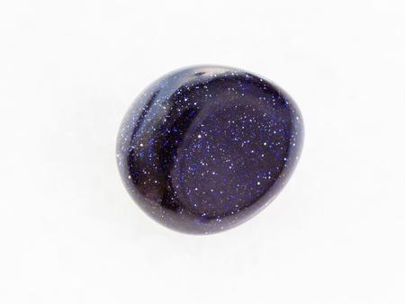 macro shooting of mineral rock specimen - polished blue goldstone gemstone on white marble background