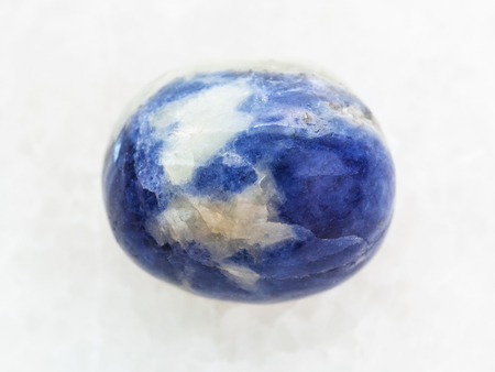 macro shooting of natural mineral rock specimen - tumbled Sodalite gem stone on white marble background
