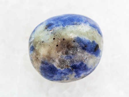 macro shooting of natural mineral rock specimen - polished Sodalite gem stone on white marble background Stock Photo