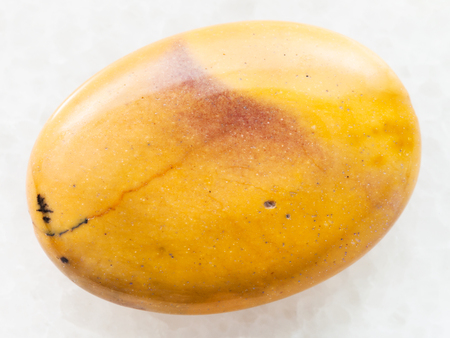macro shooting of natural mineral rock specimen - bead from yellow Mookaite (Mookaite Jasper) gemstone from Australia on white marble background