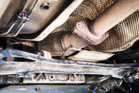 repairing of corrugation muffler of exhaust system in car workshop - bottom view of old broken corrugation muffler on car 스톡 콘텐츠