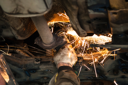 repairing of corrugation muffler of exhaust system in car workshop - serviceman cleans the muffler pipe on car by angle grinder Stock Photo