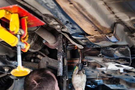 repairing of corrugation muffler of exhaust system in car workshop - repairer welds the silencer on car by argon welding